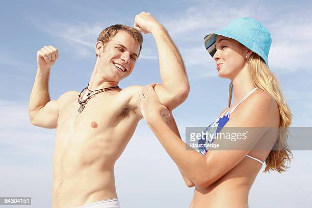 Young man flexing muscles for girlfriend