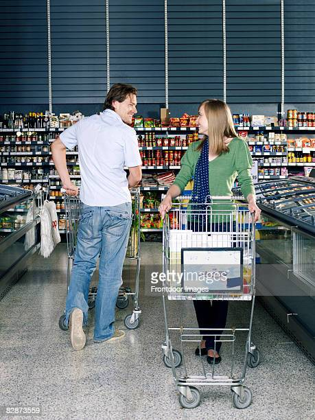 young man flirting with young woman in supermarket
