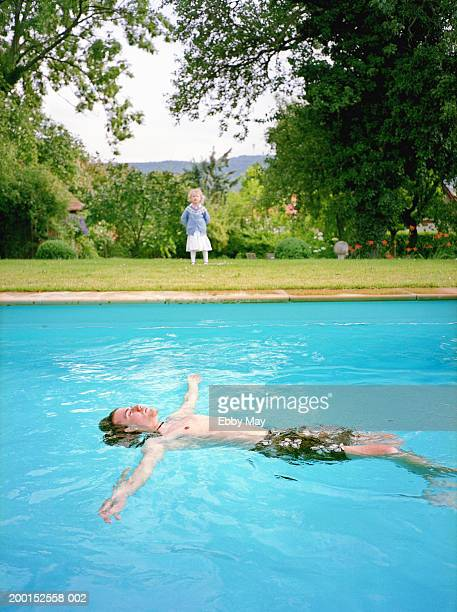 Young man floating in swimming pool, girl (2-4) in background