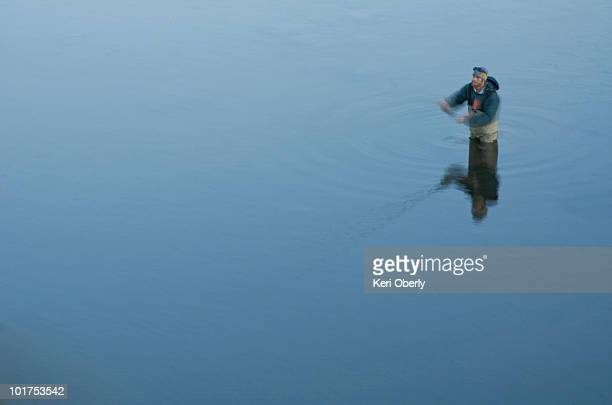A young man fly fishes in flat, freezing cold water, on the Truckee River, California.