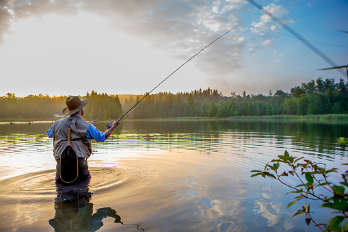 Young man flyfishing at sunrise 582310010