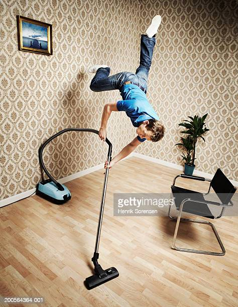 Young man flying and vacuuming floor