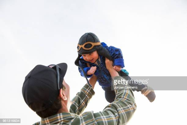 A young man flying his baby in the air.