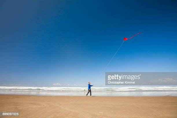 A young man flys a red kite in the sky while walking a beach along the Oregon Coast