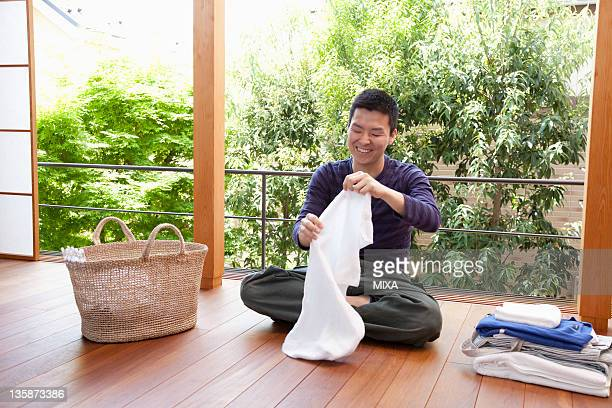 Young man folding laundry