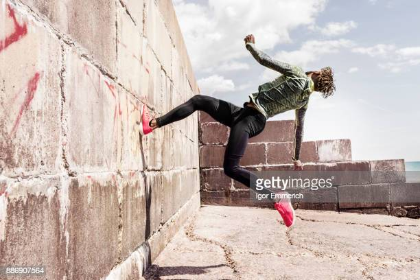 young man, free running, outdoors, running up side of wall - dobrável - fotografias e filmes do acervo