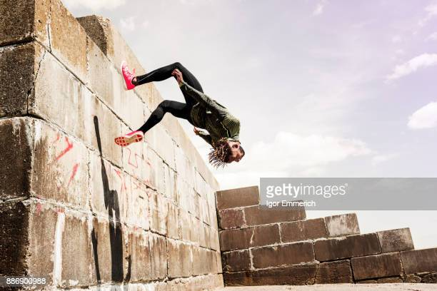 young man, free running, outdoors, somersaulting from side of wall - le parkour stock-fotos und bilder