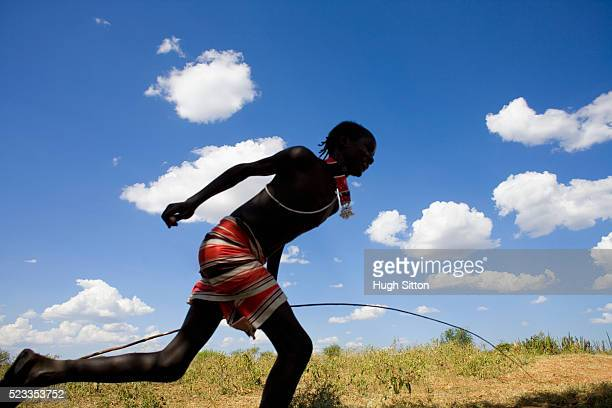 young man from hamer tribe running in meadow - hugh sitton stock-fotos und bilder