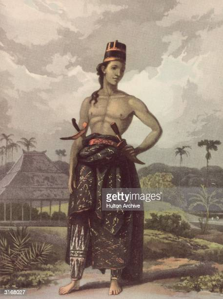A young man from Java wearing court dress with two knives tucked into his belt Coloured aquatint from Raffles 'History of Java'