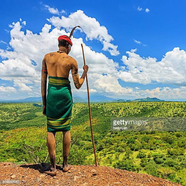hombre joven de tribu mursi observando a, etiopía, áfrica - tribu mursi fotografías e imágenes de stock
