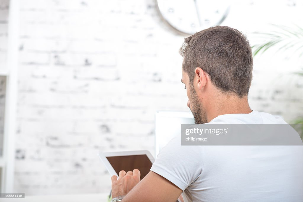 Junger Mann auf der Rückseite, die auf der Suche an einem tablet arbeitet : Stock-Foto