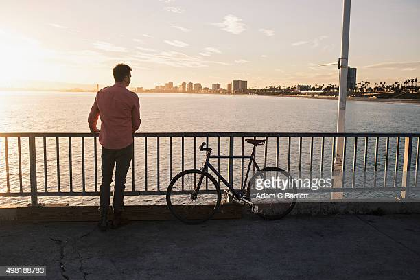 Young man gazing from pier, Long Beach, California, USA
