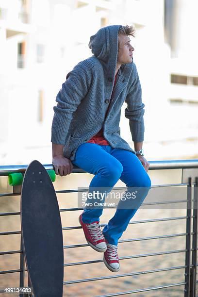 Young man gazing from riverside railings