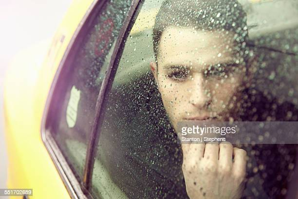 Young man gazing out of yellow cab window in rain