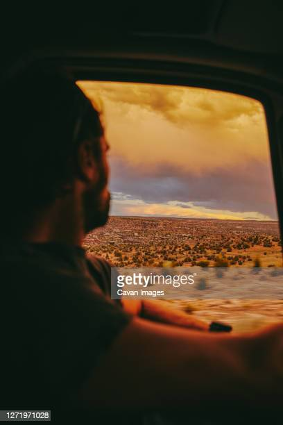 young man gazing out to sunset while driving in desert of moab, utah. - utah stock pictures, royalty-free photos & images