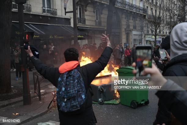 A young man gestures in front of burning dustbins which obstruct the street during a protest of students against police brutality following the...