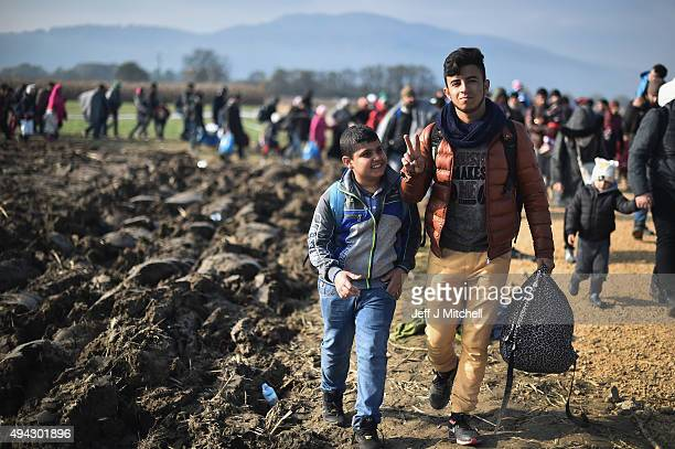 Young man gestures with a victory sign as he and other migrants are escorted by police through fields towards buses which will take them to Brezice...
