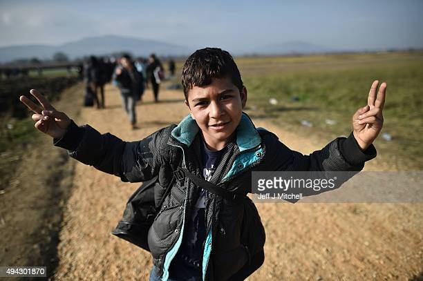A young man gestures with two victory signs as he and other migrants are escorted by police through fields towards buses which will take them to...
