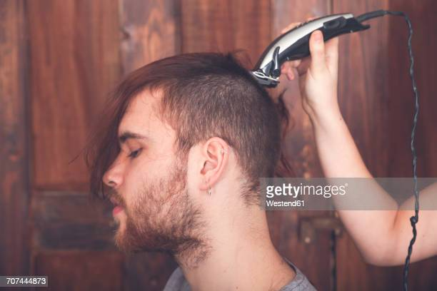 young man getting a haircut by his girlfriend with hair cutting machine - shaved head stock pictures, royalty-free photos & images