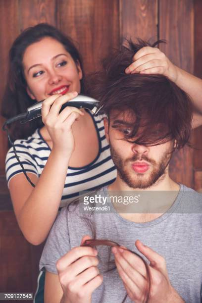 young man getting a haircut by his girlfriend with hair cutting machine - boyfriend stock pictures, royalty-free photos & images