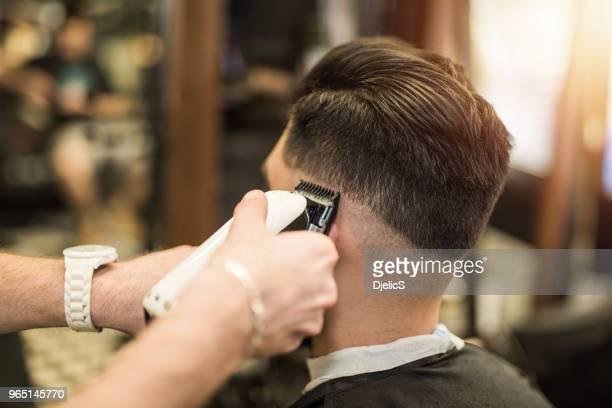 jovem, recebendo um corte de cabelo moderno. - estilo de cabelo - fotografias e filmes do acervo