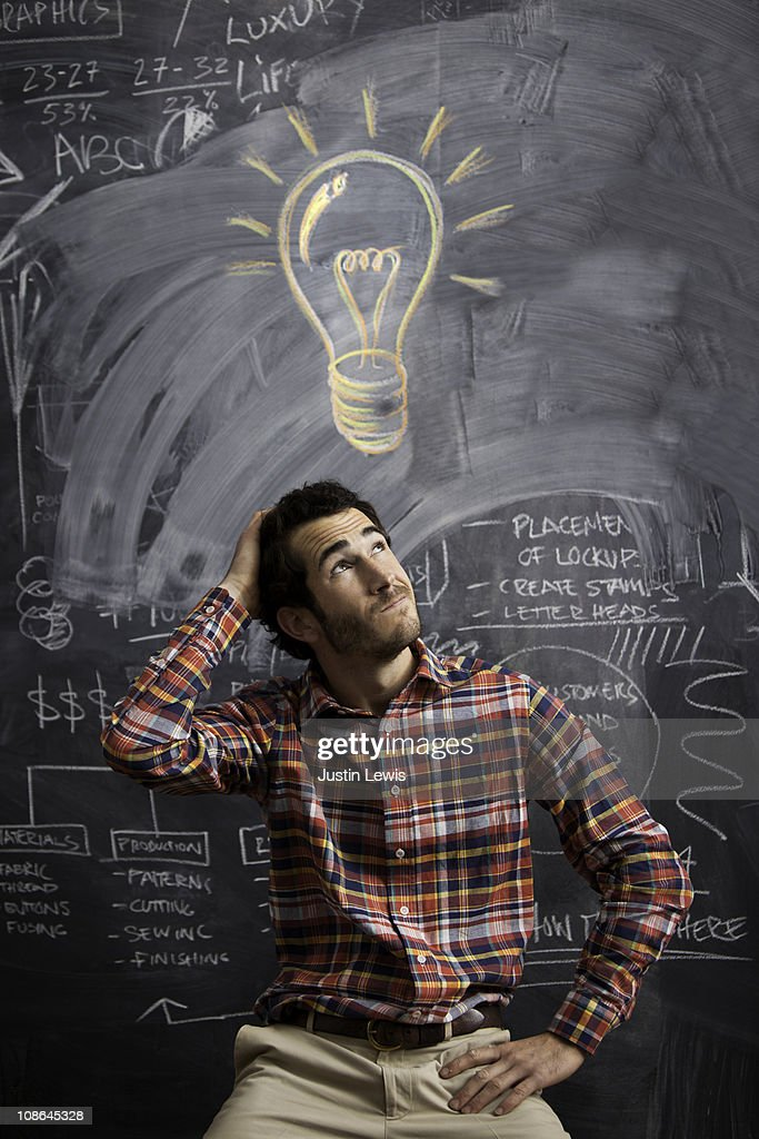 young man getting an idea with light bulb above : Stock Photo