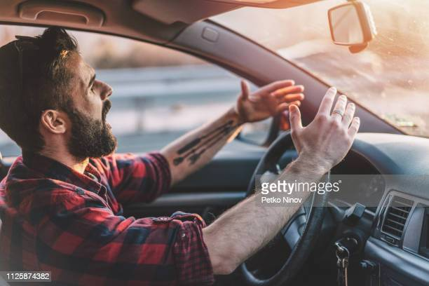 young man getting angry on the road - irritation stock pictures, royalty-free photos & images