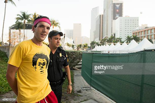 young man getting arrested by police outside ultra music festival - ultra music festival stock pictures, royalty-free photos & images