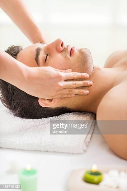 joven de recibir masaje facial en el spa. - masaje hombre fotografías e imágenes de stock
