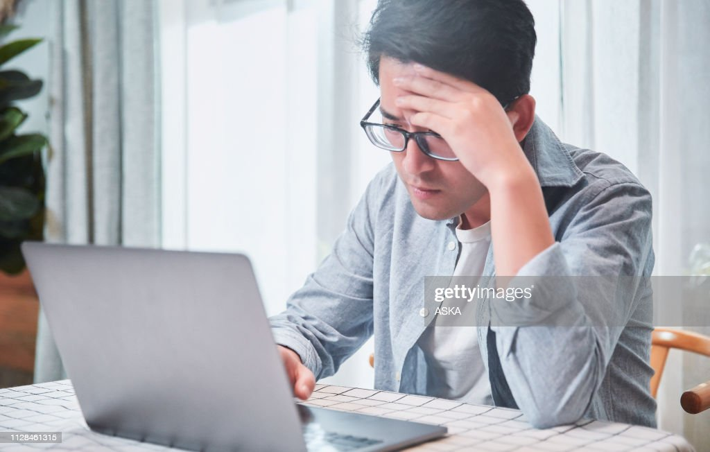 Young man getting frustrated over laptop : Stock Photo