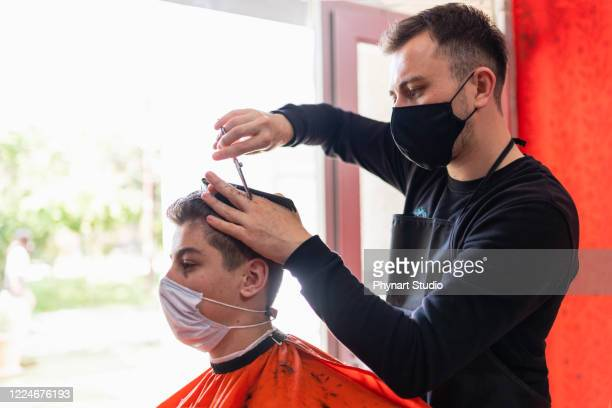 young man getting haircut at the barbershop - hairstyle stock pictures, royalty-free photos & images