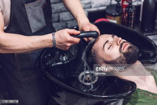 joven que se lava el pelo en los peluqueros - masaje hombre fotografías e imágenes de stock