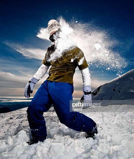 Jeune homme se faire avec Boule de neige sur les montagnes