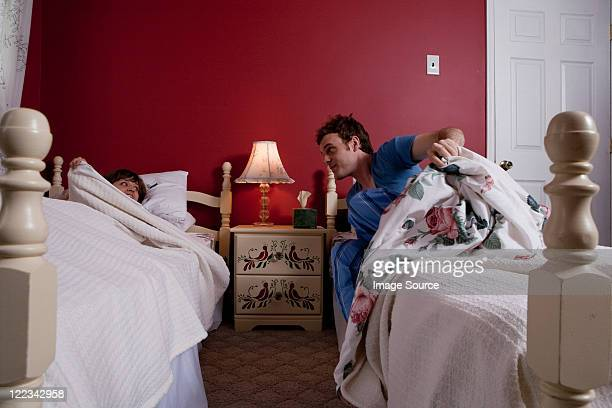 Young man getting out of bed to see young woman