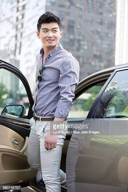 Young man getting out of his car
