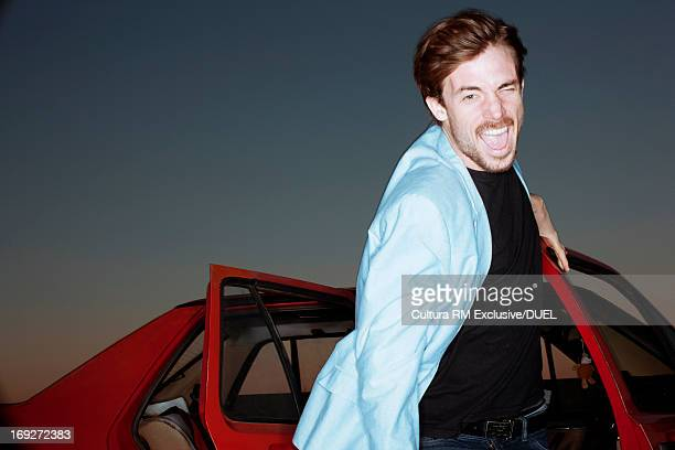 Young man getting out of red car, portrait