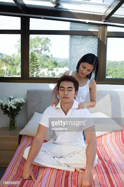 Young man getting shoulder massage from a mid adult woman