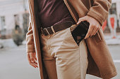 Young man getting smartphone out of his pocket