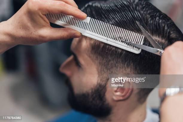 giovane uomo che sta ottenendo un taglio di capelli elegante - capelli foto e immagini stock