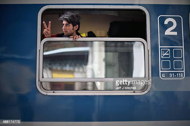 A young man gives the victory sign as his train leaves for the Austrian border from Keleti railway station on September 14 2015 in Budapest Hungary...