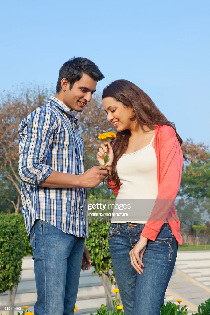 Young man giving a flower to a young woman : Stock Photo