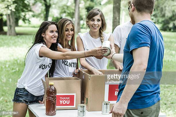 young man giving food can to volunteers - pjphoto69 stock pictures, royalty-free photos & images