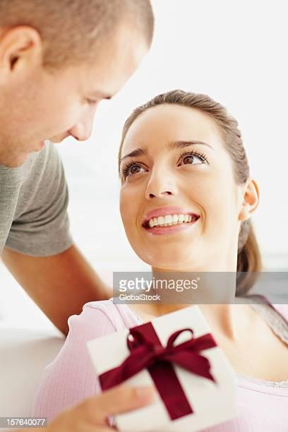 Jeune homme souriant, donnant à son partenaire cadeau