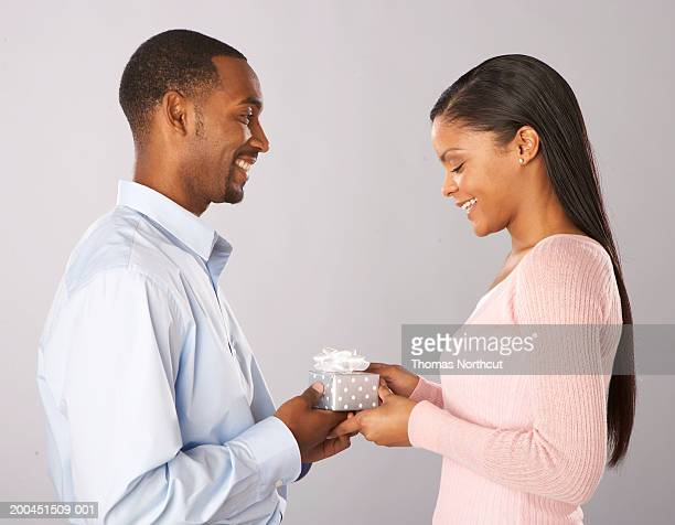 Young man giving gift to young woman, smiling, side view
