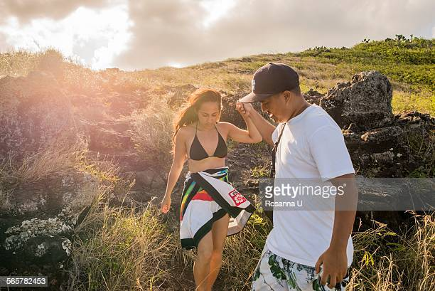 Young man giving girlfriend a helping hand on Makapuu coast path, Oahu, Hawaii, USA