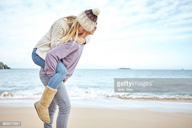 Young man giving girlfriend a piggyback on beach, Constantine Bay, Cornwall, UK