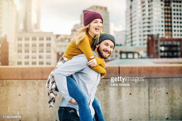 young man giving girlfriend a piggyback on city rooftop terrace - piggyback stock pictures, royalty-free photos & images