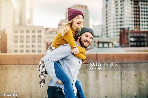 young man giving girlfriend a piggyback on city rooftop terrace - portare a cavalluccio foto e immagini stock