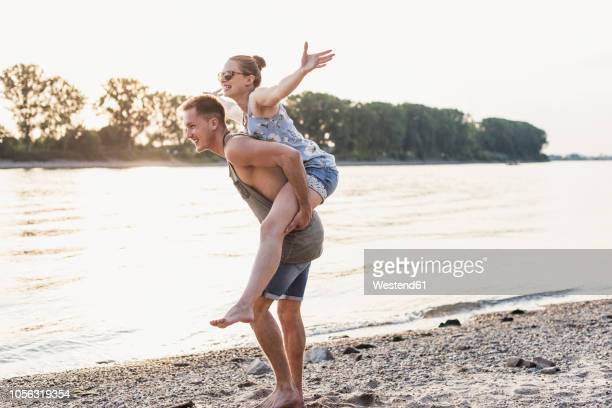 young man giving girlfriend piggyback ride at the riverbank - piggyback stock photos and pictures