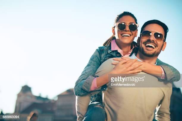 young man giving his girlfriend piggyback ride outdoors - occhiali da sole foto e immagini stock